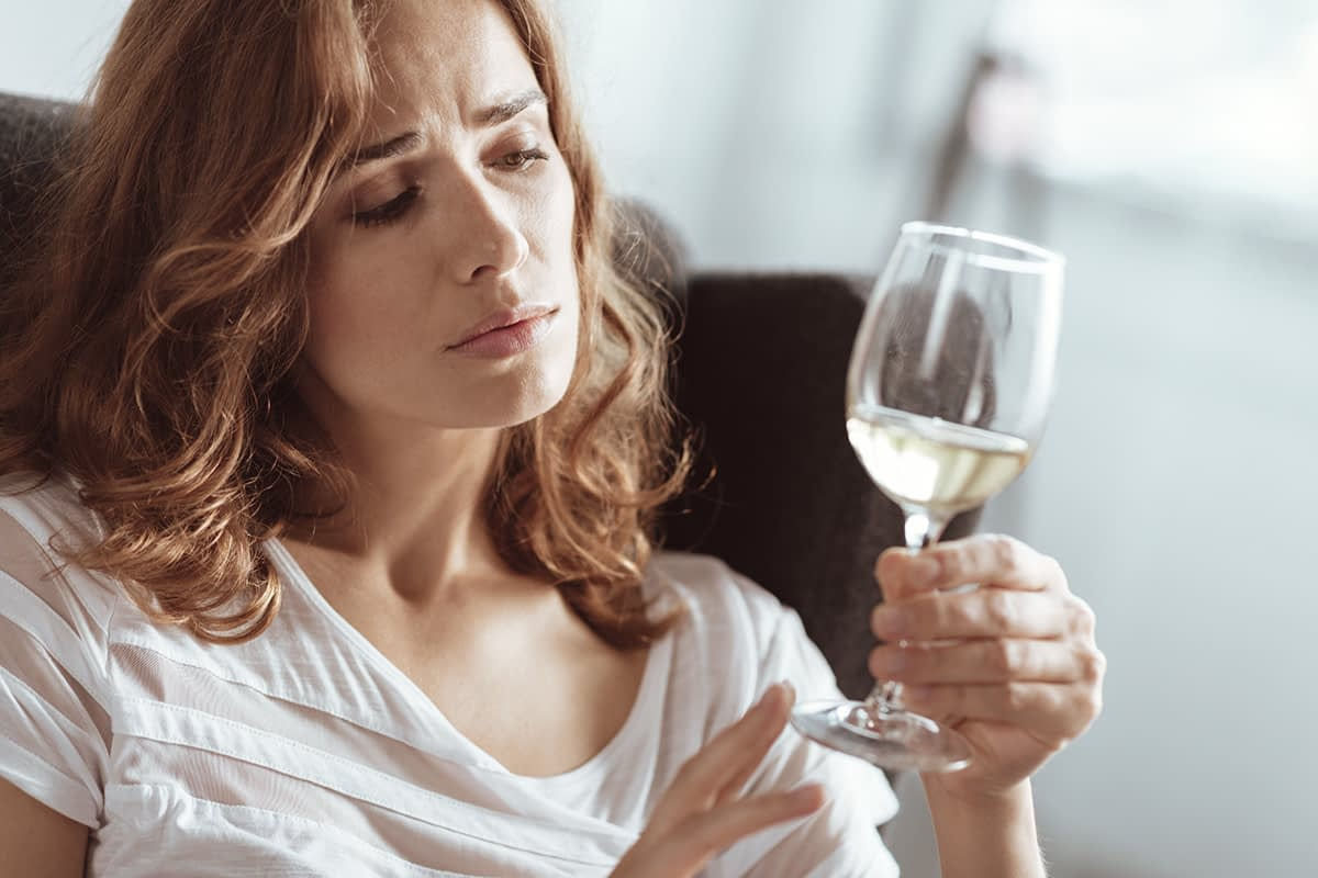 a woman holds a glass of wine and thinks about the signs of an alcohol addiction