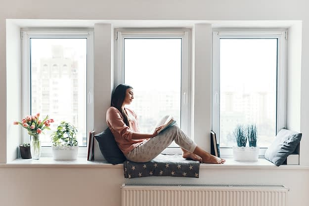 a woman sits on a window seat and reads about relapse prevention techniques