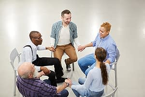a group of people join hands at a 12 step rehab center
