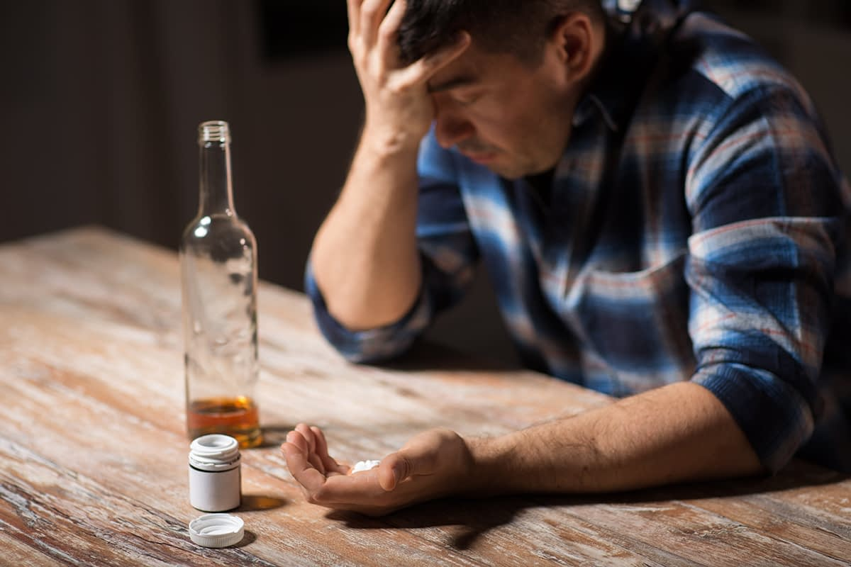 a man sits in front of a bottle of alcohol and a pill bottle and considers taking benzos and alcohol together