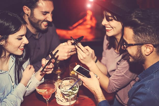 a group of people use their phones to research drinking and social media while they're out on the town