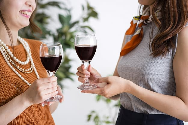 two mothers drink together as part of wine mom culture