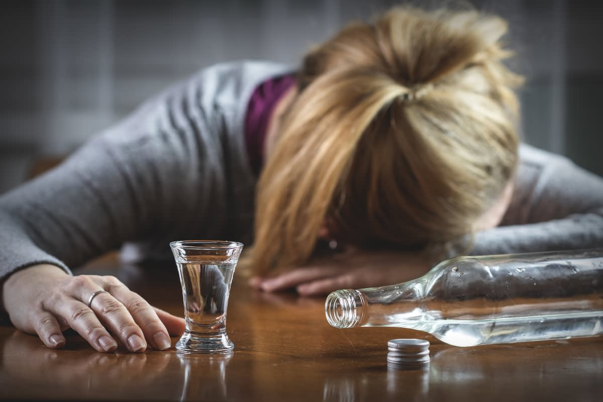 a woman puts her head down in front of a bottle of clear liquid as she considers the link between alcohol and depression
