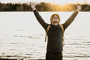 a man cheers next to a lake as he considers a men's rehab program in ca
