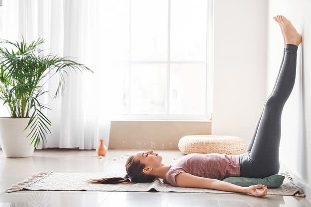 a woman practices yoga as one of her stress management techniques