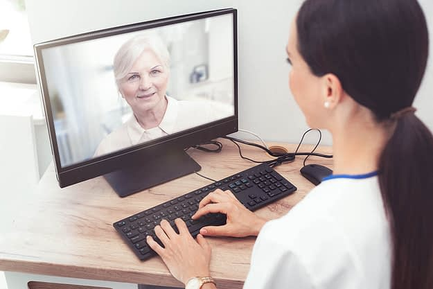 woman on computer receiving telehealth services