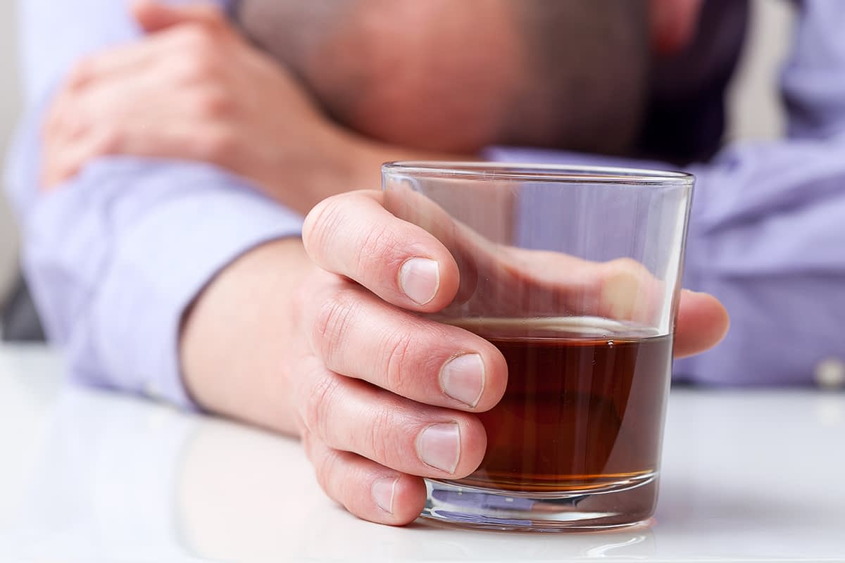 man with head down showing signs of alcoholism