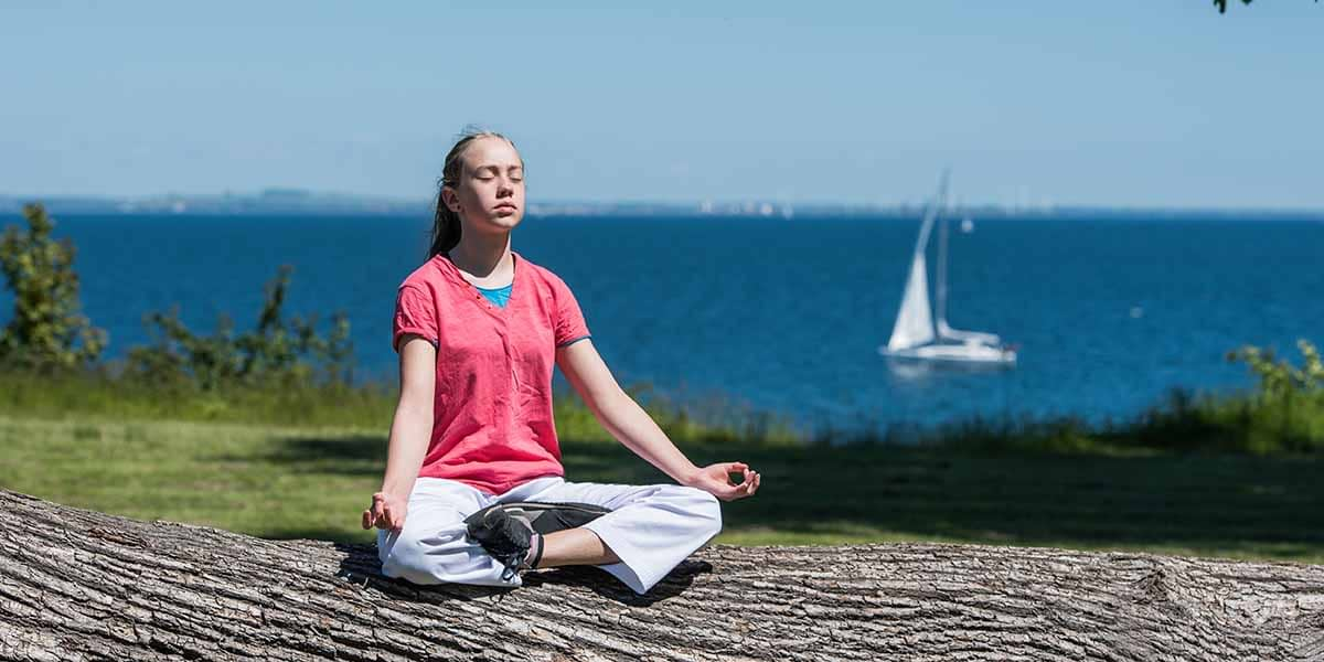 woman practicing mindfulness by the sea