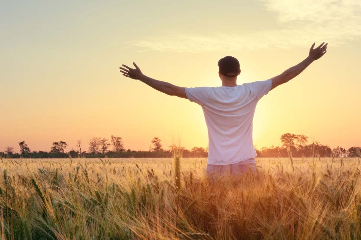 a man stretches out his arms towards the sunrise as he experiences sober living