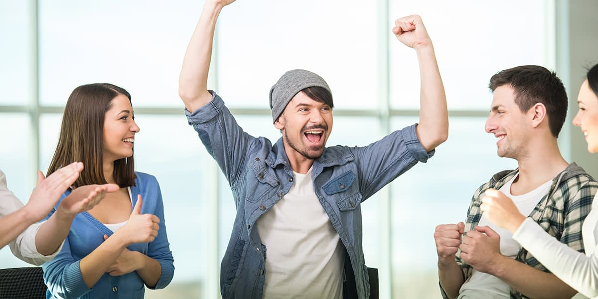 A man cheering in group therapy because he has a support system for recovery
