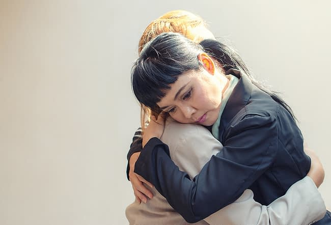 a woman hugging her child after learning dependence vs addiction