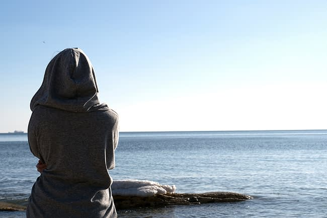 a woman looking at a lake thinking about drug addiction rehab center