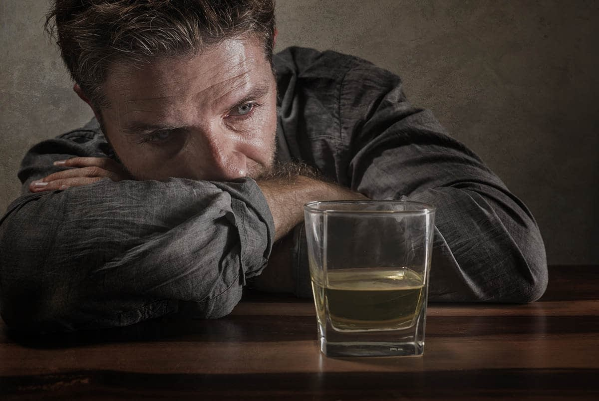 a man suffering from triggers of drinking