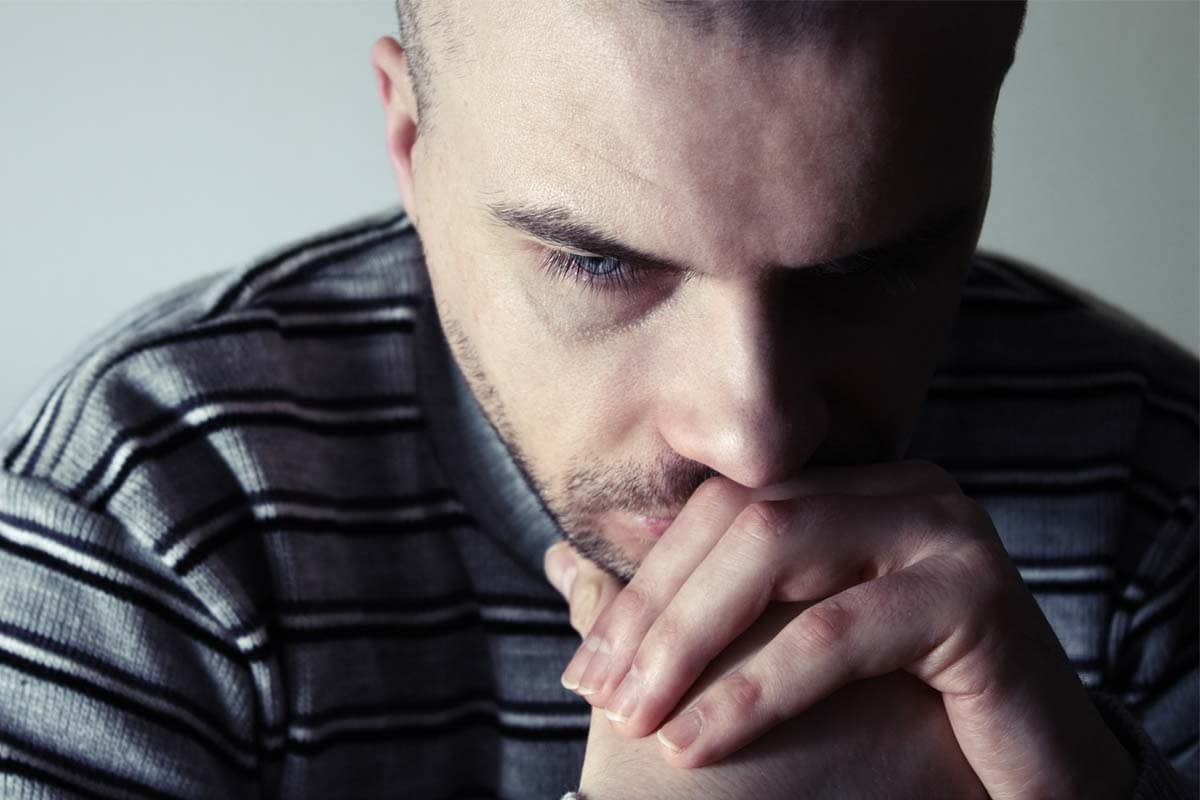 a man rests his chin on folded hands and wonders how to stop a friend from committing suicide