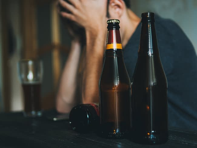Man dealing with symptoms of alcohol use disorder