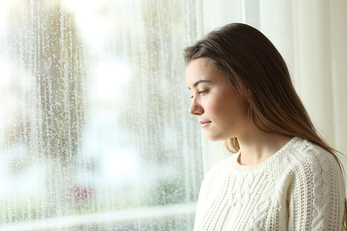 a woman looking out a rainy window thinking about signs of stress