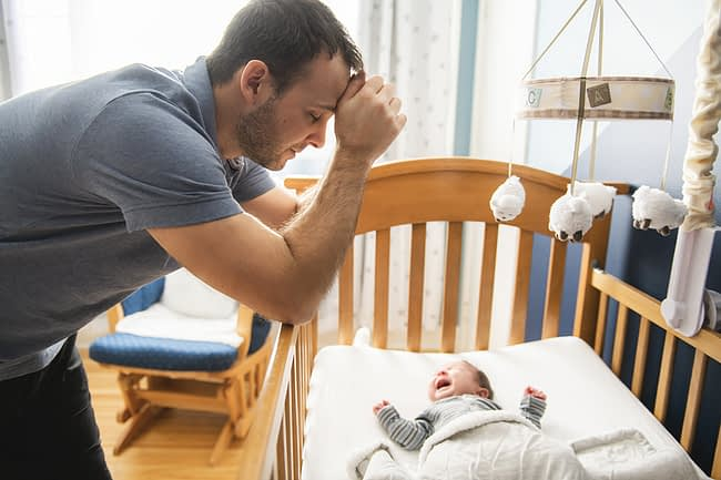 man leaning against his baby's crib suffering from symptoms of postpartum depression for men