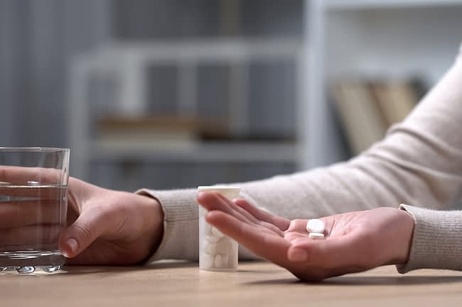 a person taking pills who needs a painkiller rehab