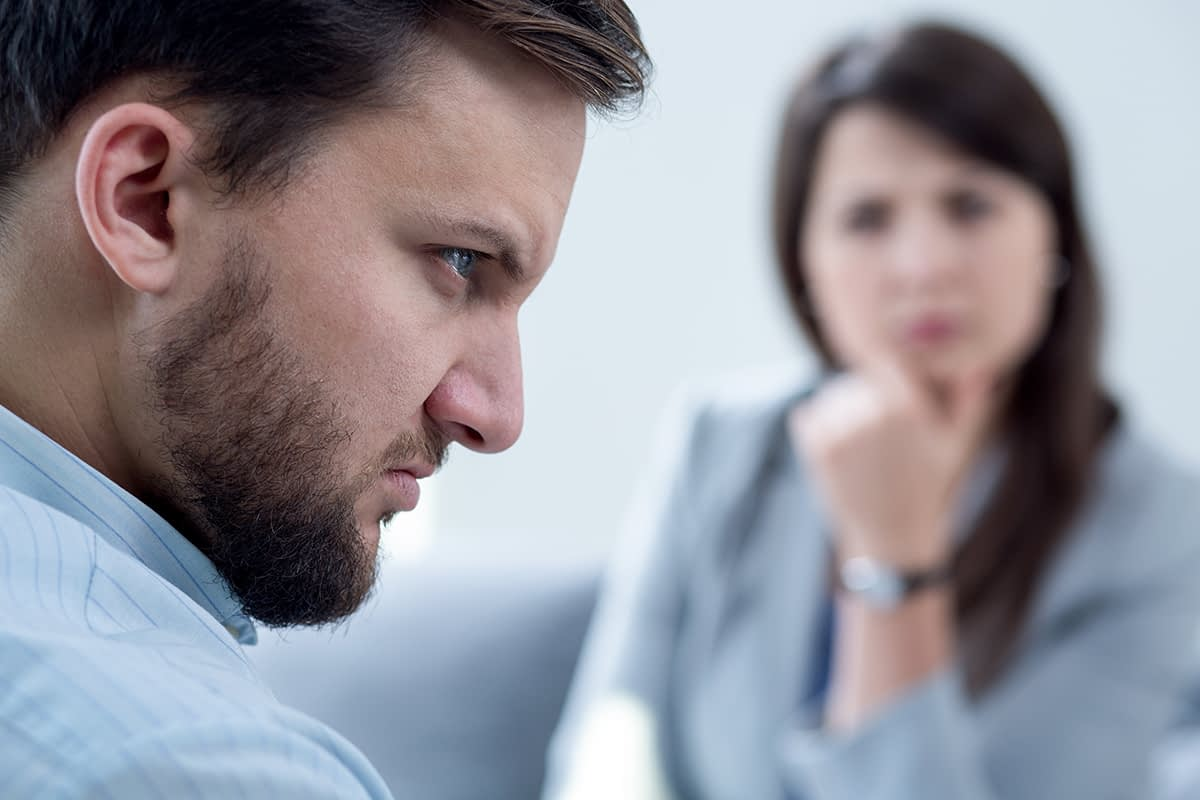 a man upset as he talks to his doctor during contingency management therapy