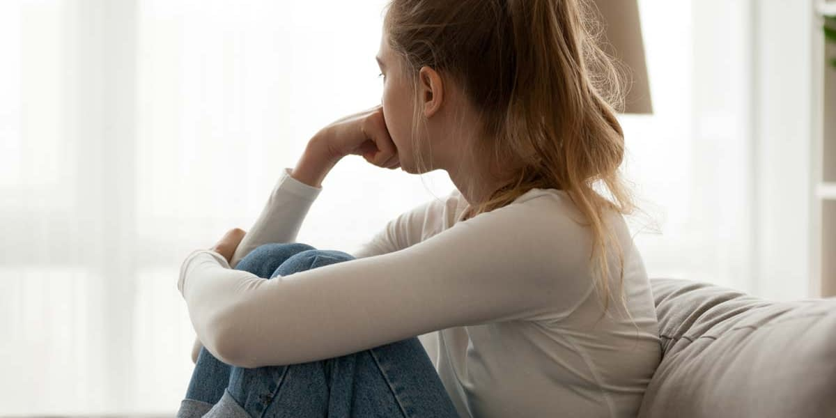 a young woman sits on a couch and considers the effects of an eating disorder