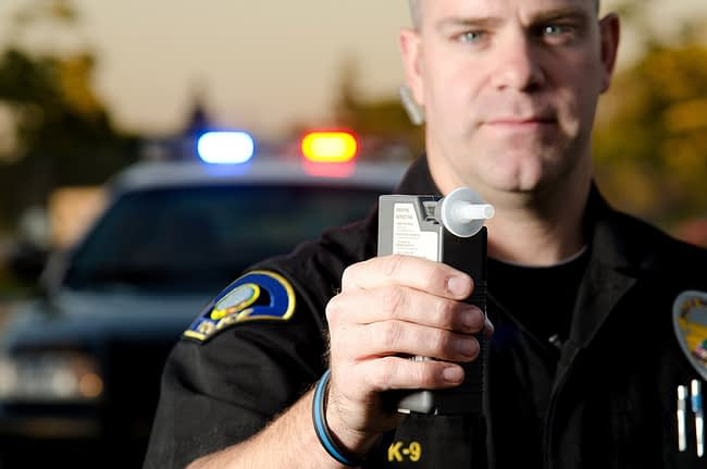 a police officer holding a breathalyzer to test for dui vs dwi