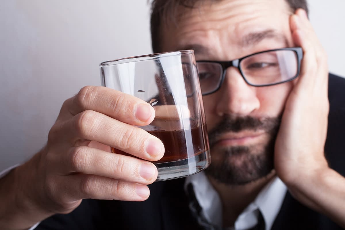 a man drinking and suffering from Stages of Alcoholism