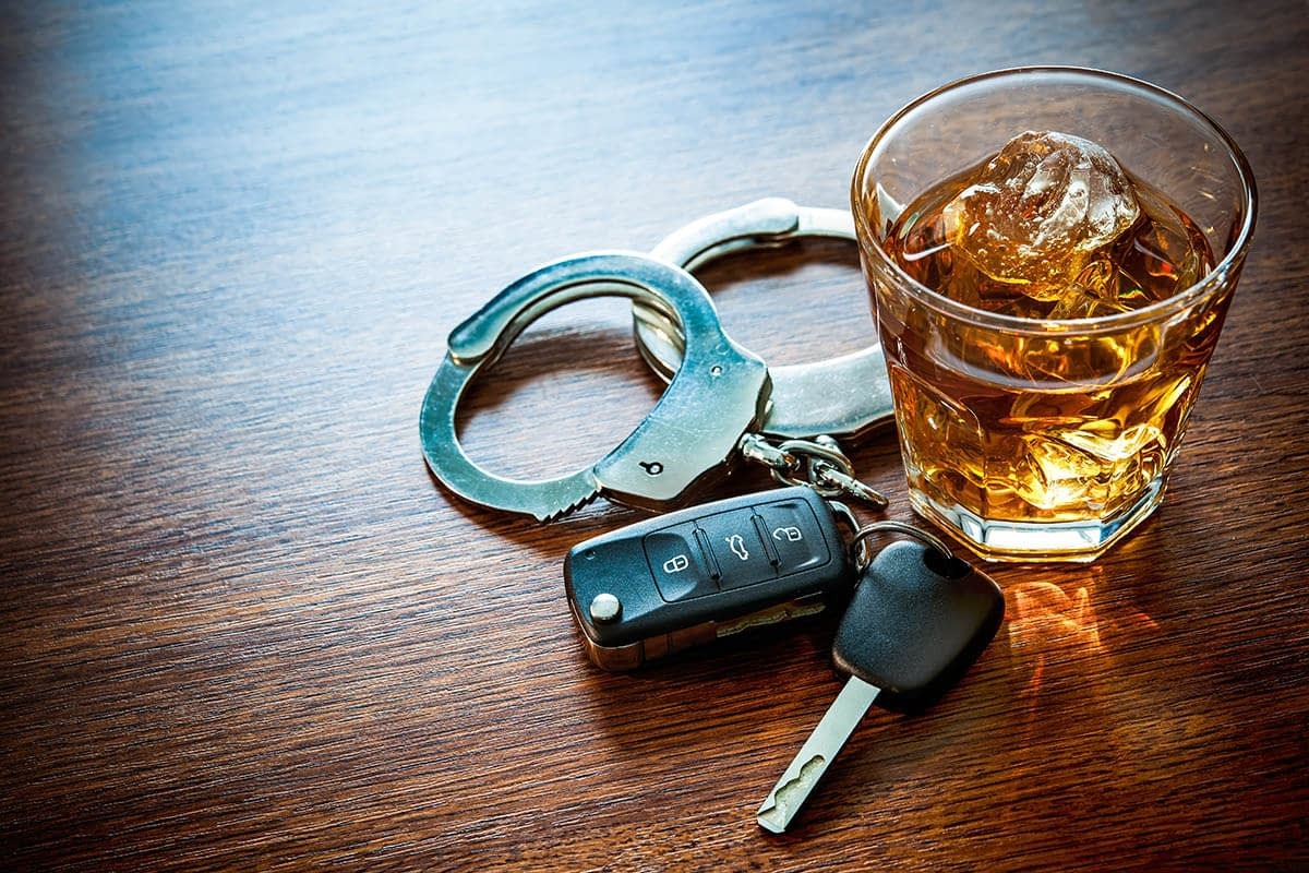Car keys and glass of alcohol on table leads to the question of the difference between dui vs dwi