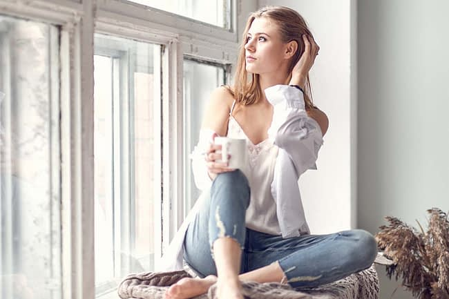 a woman sits by a window and drinks coffee as she thinks about going to detox