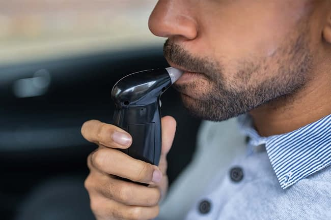 a man uses a breathalyzer after drunk driving