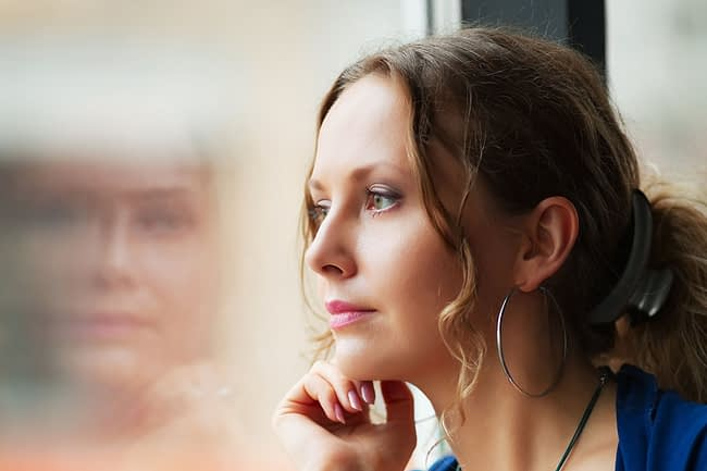 a woman looking out the window thinking about stress management