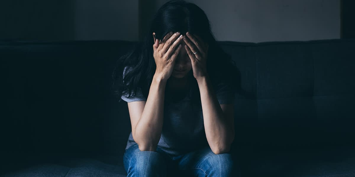 a woman stress on the couch thinking about triggers of drug use