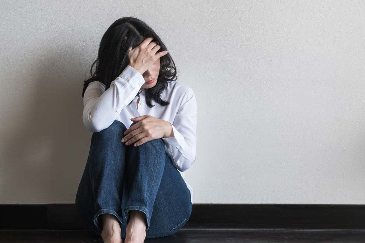 a woman sits against a wall with her head in her hand as she considers the suicide contagion