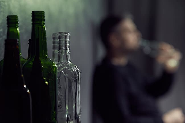 a man drinking despite knowing the dangers of alcohol addiction