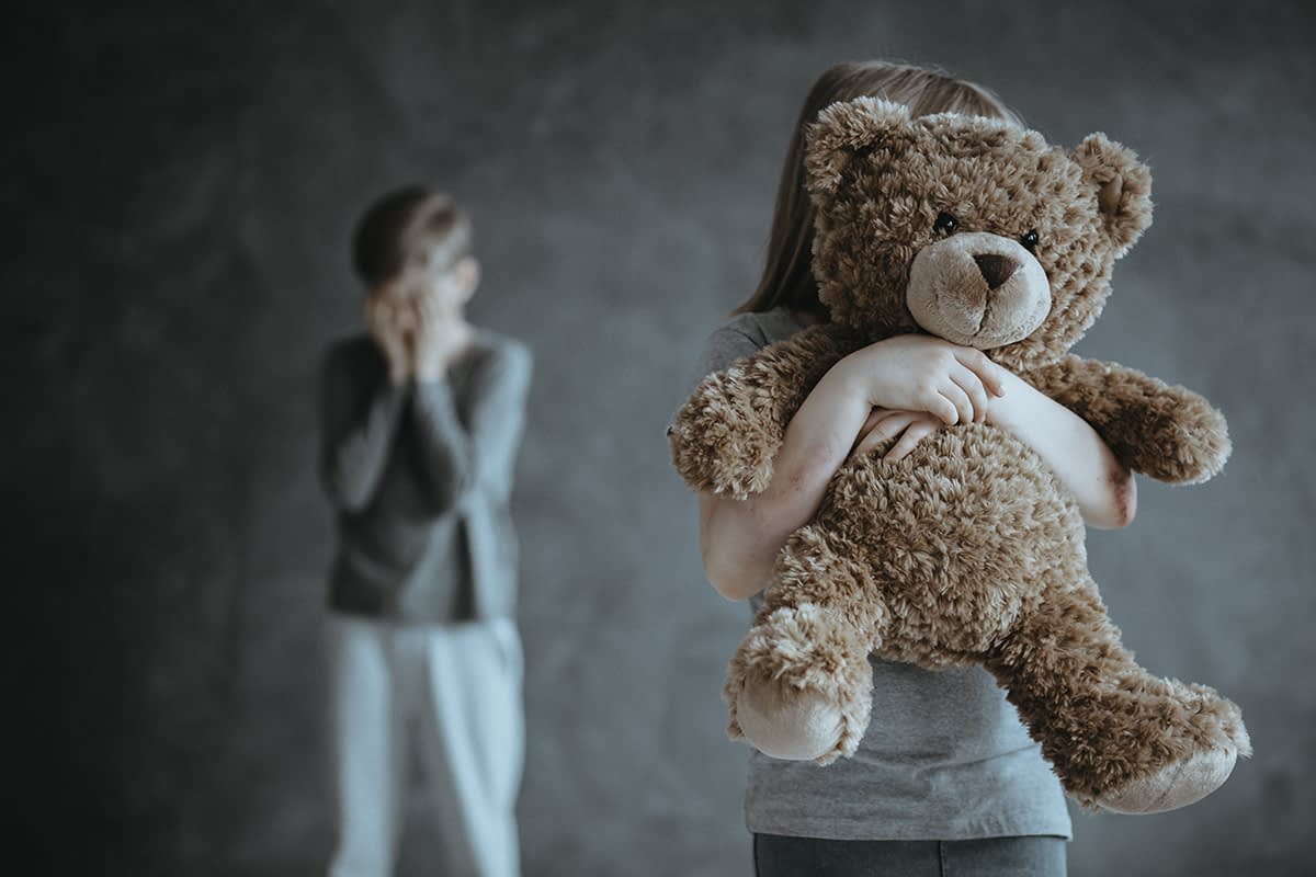 a young child holding a teddy bear while not understanding childhood trauma and addiction