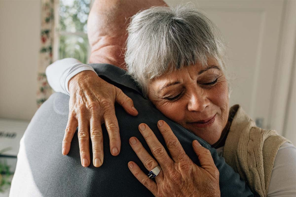 a woman hugs her husband as she considers the effects of obsessive love disorder