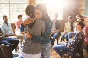 two women hugging during a group therapy session at a drug rehab near seattle