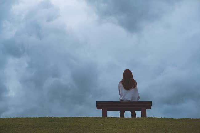 a woman looking at a storm while experiencing signs of stress