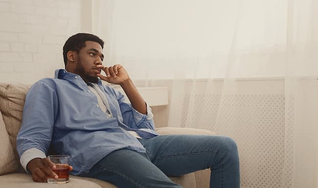 a man sitting at home thinking about the risks of drinking alcohol