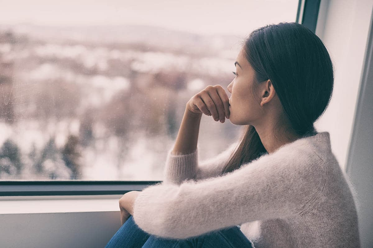 a woman looking out a window struggling from signs of depression