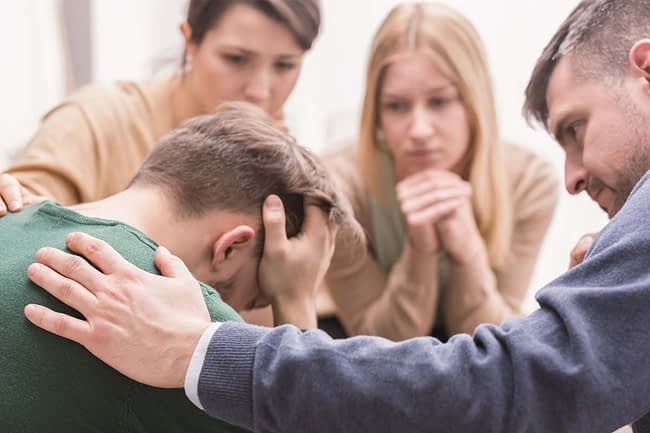 a family gathers around a man during an intervention
