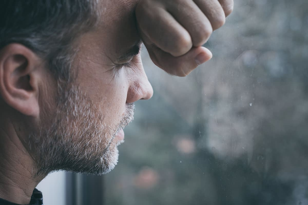 a man looking out the window thinking about dependency vs addiction
