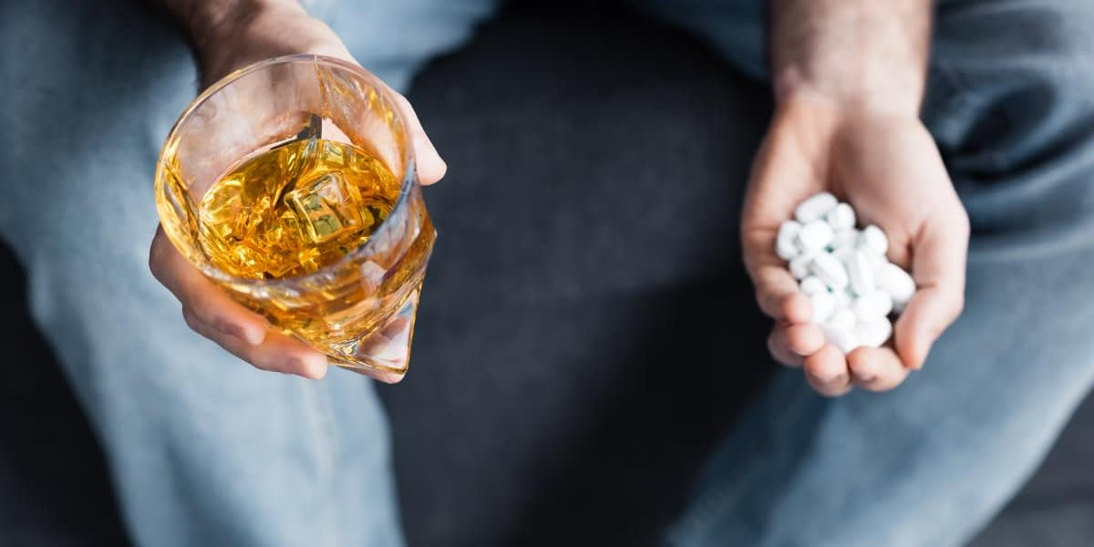 man holding alcohol and a handful of pills