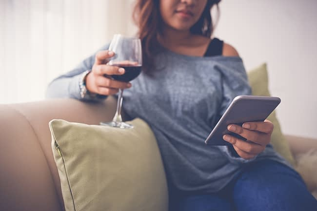 a woman reading unaware of the connections between drinking and social media