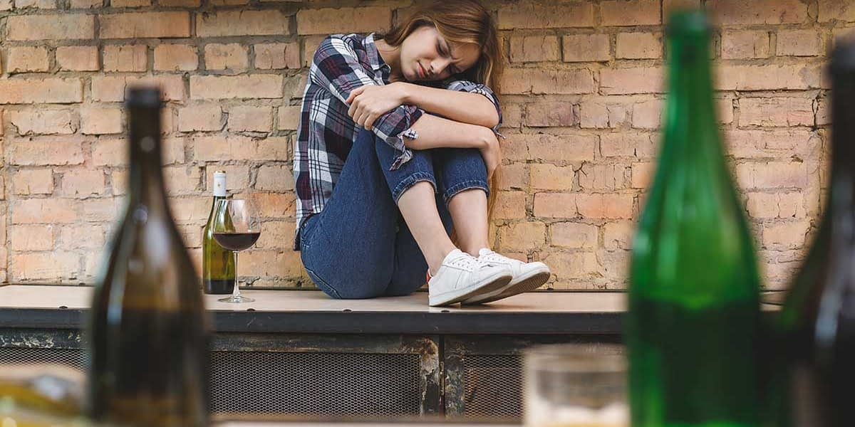 a woman feeling upset while thinking about alcoholism and anxiety
