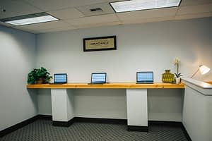 Row of communal laptops in an office at Bayview Recovery Center