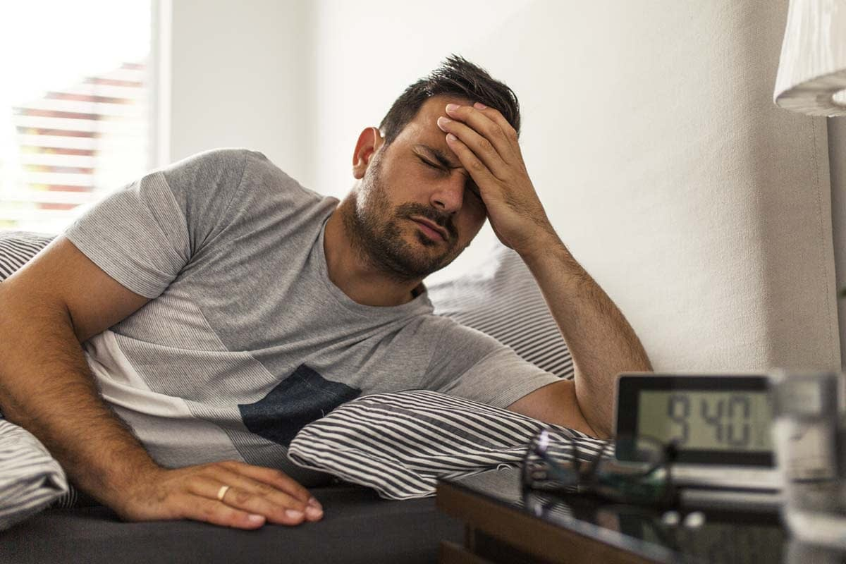a man suffering from a hangover wonders if he is an alcoholic