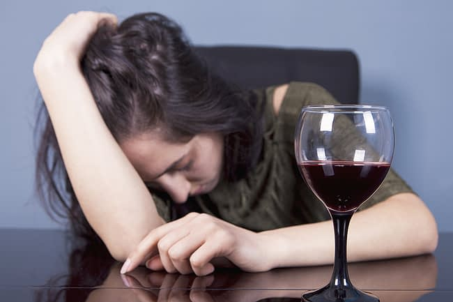 a woman feeling ill after experiencing the dangers of binge drinking