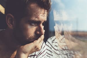 Sad man reflected in a window contemplated his drug abuse definition.