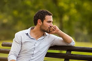 Worried man on park bench concerned about his relapse prevention plan.