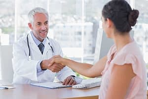 Doctor shaking hand of woman across desk asking about the detoxification process